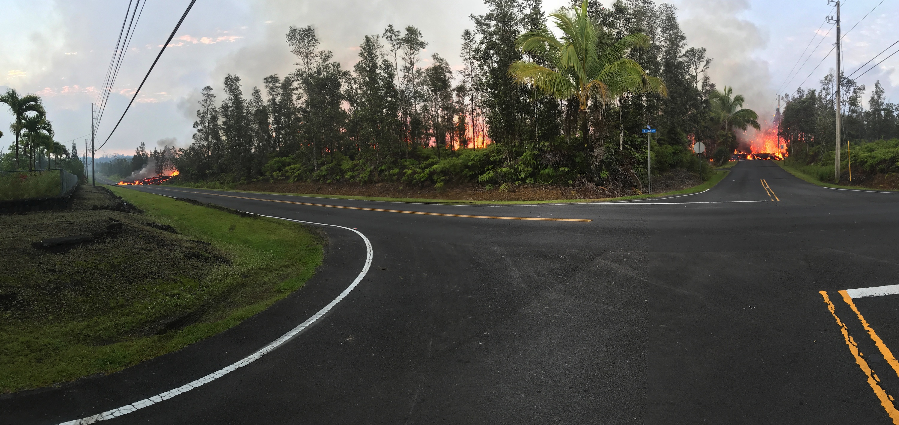 panorama of street intersection showing low wall of cooled lava and spatter in distance, cutting across roads and into trees