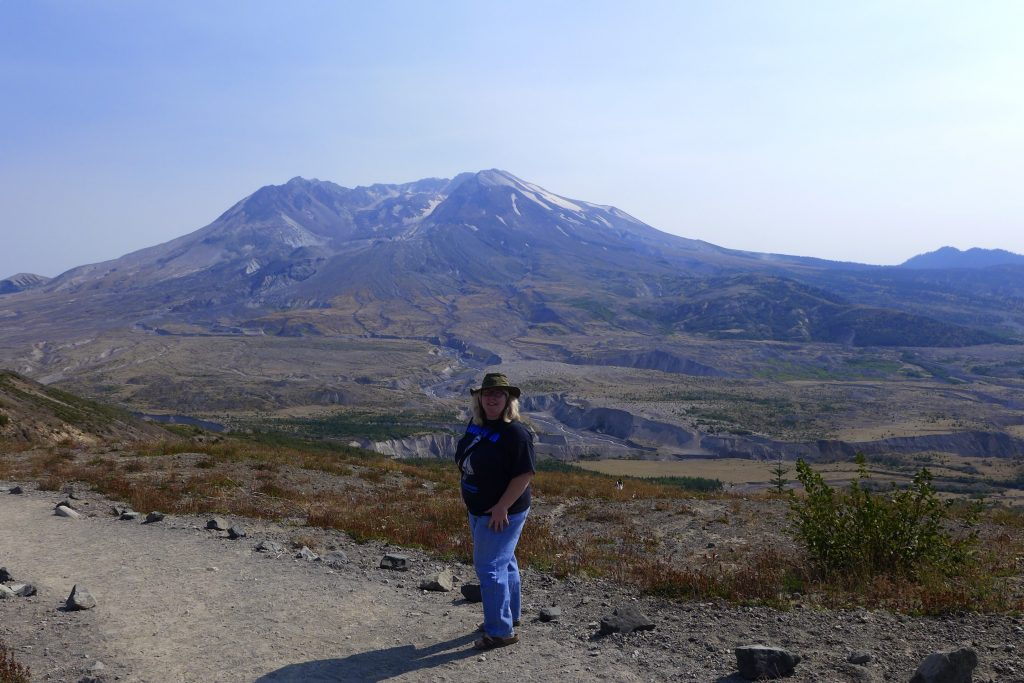 Person standing in front of hazy panorama of Mount St Helens surrounded by sparse vegetation, flowers